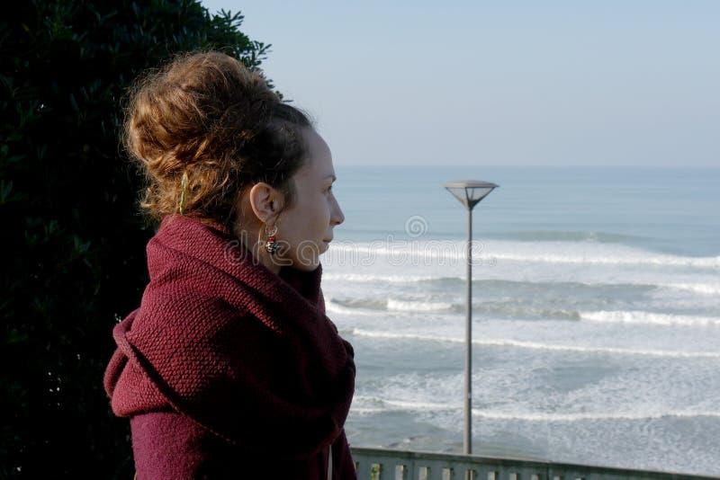Ritratto di una giovane donna che esamina il mare fotografia stock