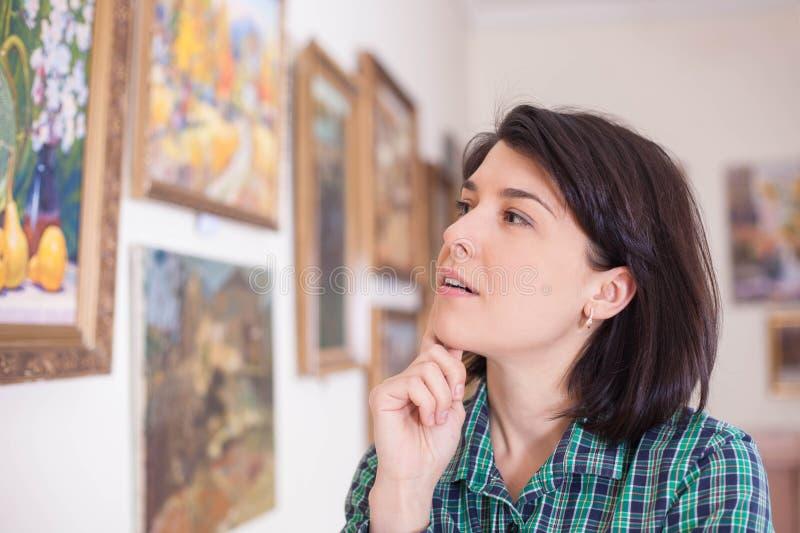 Ritratto di una giovane donna che esamina una pittura in una galleria di arte o in un museo fotografia stock libera da diritti