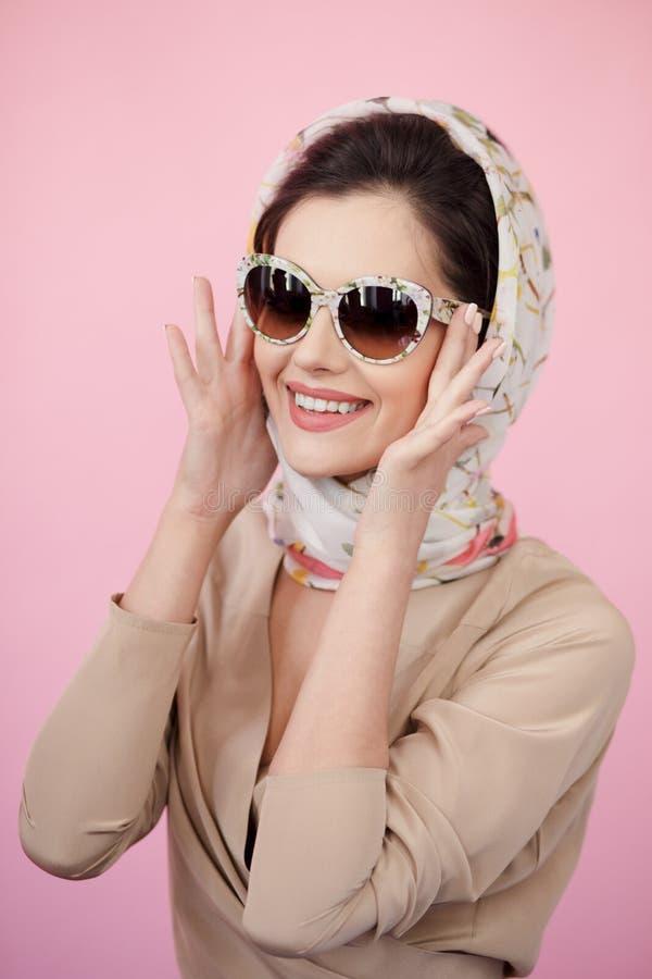 Ritratto di una giovane donna che indossa i vestiti eleganti, occhiali da sole, tocca i suoi vetri con le sue mani, fondo rosa fotografia stock