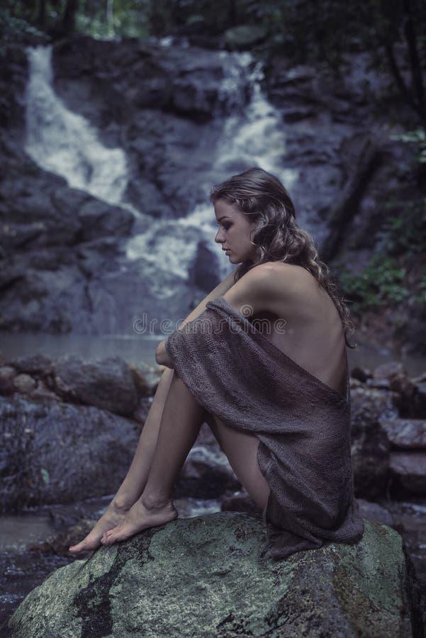 Ritratto di una giovane donna che medita su roccia fotografia stock