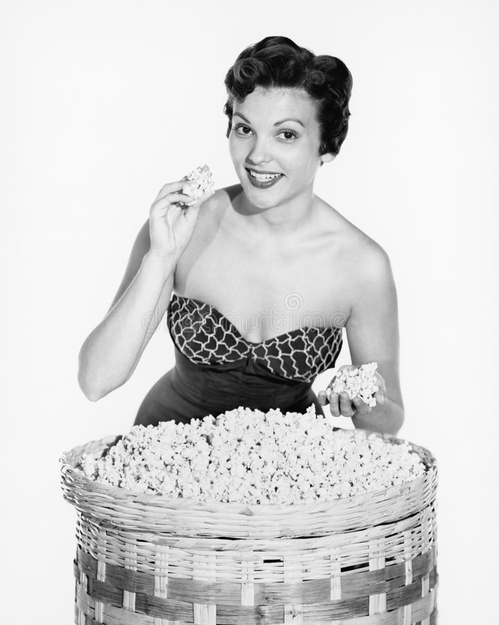 Ritratto di una giovane donna che mostra popcorn e sorridere (tutte le persone rappresentate non sono vivente più lungo e nessuna fotografie stock