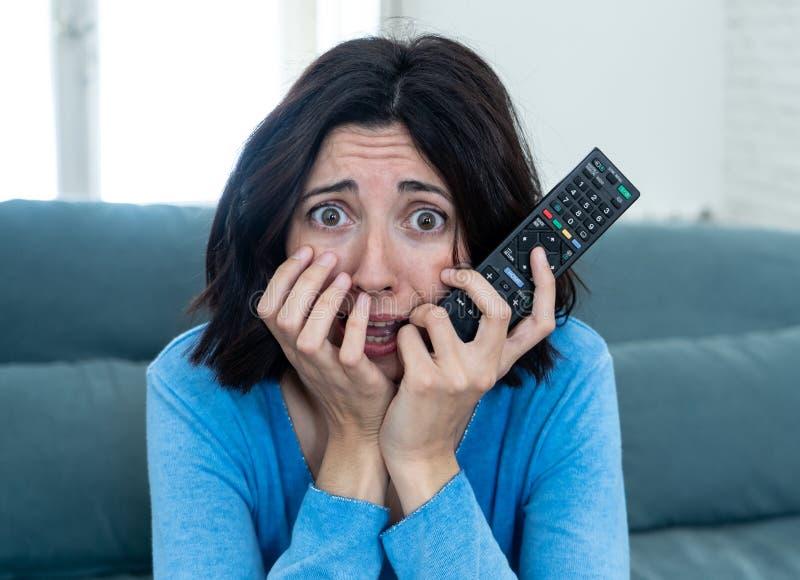 Ritratto di una giovane donna che sembra film spaventoso di sorveglianza spaventato e colpito sulla TV fotografia stock