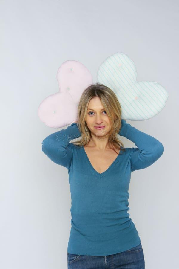 Ritratto di una giovane donna che tiene i cuscini a forma di di un cuore La ragazza ha un divertimento immagini stock libere da diritti