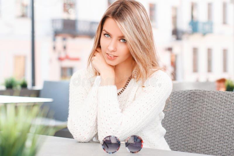 Ritratto di una giovane donna con i bei occhi azzurri con un sorriso con capelli biondi con trucco naturale in un maglione d'anna fotografia stock