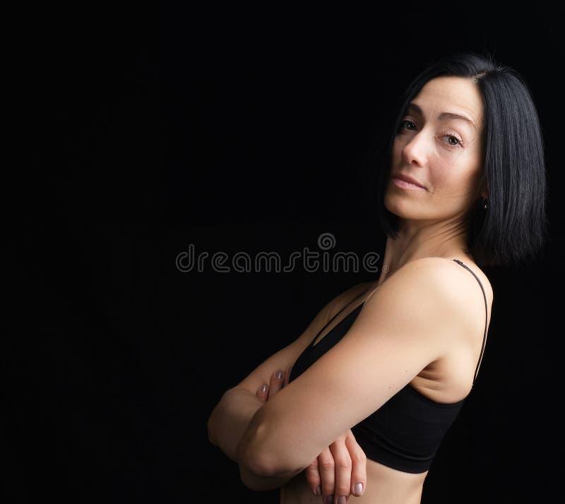 Ritratto di una giovane donna con reggiseno nero sullo sfondo scuro immagini stock libere da diritti