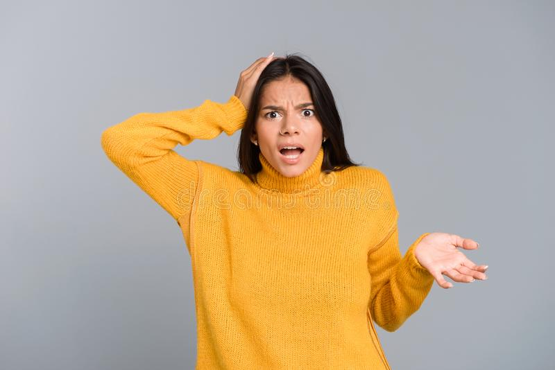 Ritratto di una giovane donna confusa vestita nella condizione del maglione isolato immagine stock