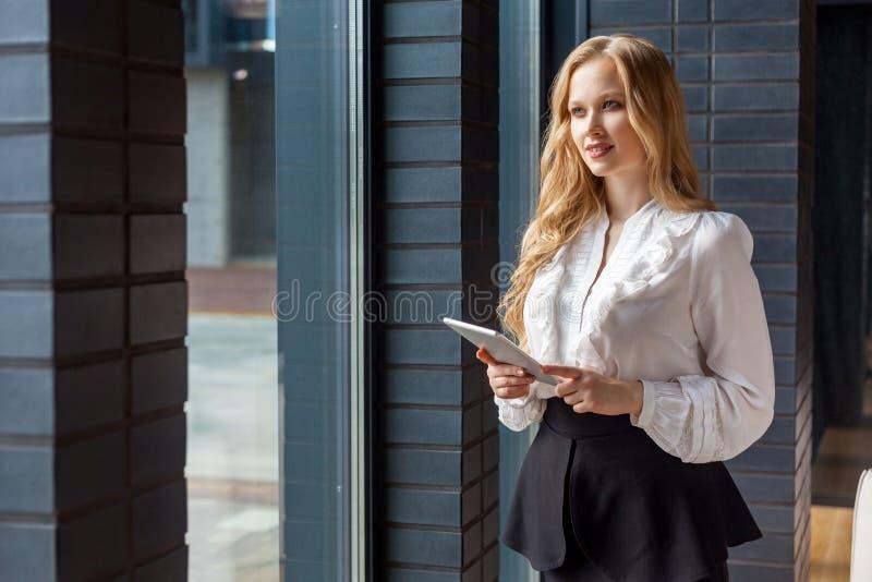 Ritratto di una giovane donna d'affari con i capelli biondi in una elegante camicia classica che guarda fuori dalla finestra e so fotografie stock libere da diritti
