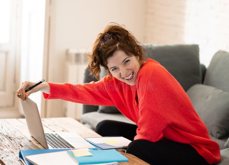 Ritratto di una giovane donna felice che lavora al computer portatile che si siede sul sof? Nel lavoro e nel concetto di studio fotografie stock libere da diritti