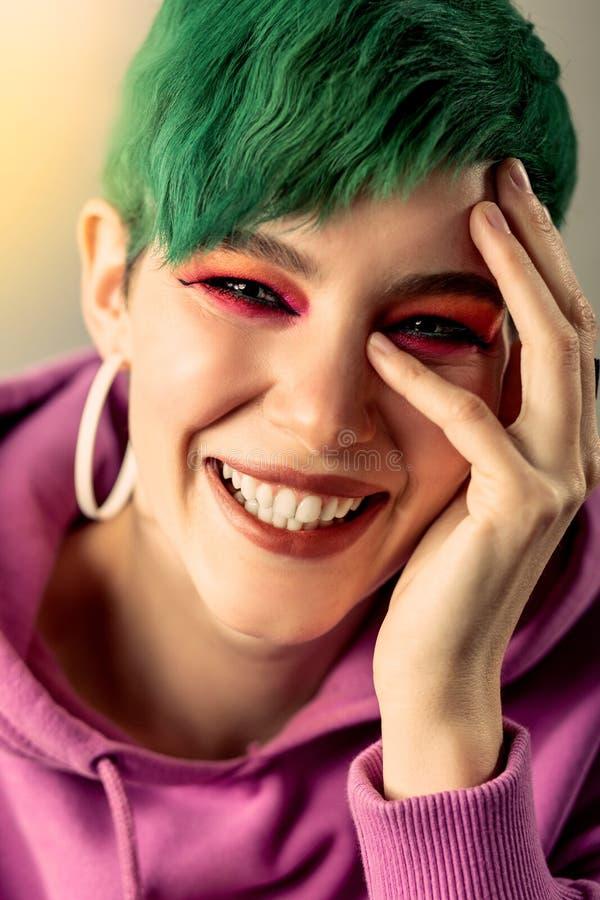 Ritratto di una giovane donna felice che tocca il suo fronte fotografie stock