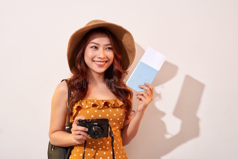 Ritratto di una giovane donna felice nella macchina fotografica della tenuta del cappello e nel passaporto di mostra mentre stand fotografia stock