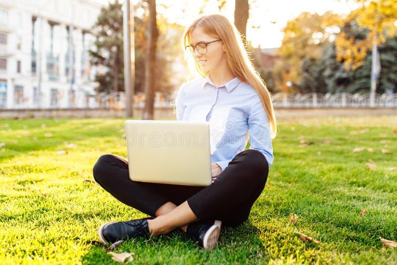 Ritratto di una giovane donna graziosa con i vetri che si siedono sul g verde immagine stock libera da diritti