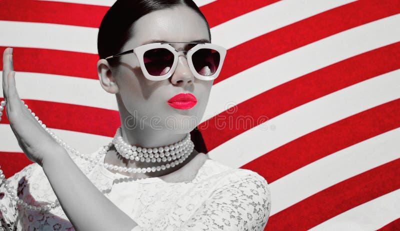 Ritratto di una giovane donna graziosa in dess bianchi del pizzo, collana bianca della perla ed occhiali da sole con le labbra di fotografie stock libere da diritti