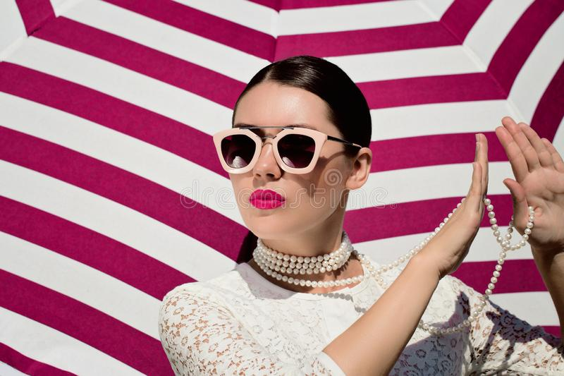 Ritratto di una giovane donna graziosa in vestito bianco dal pizzo, collana bianca della perla ed occhiali da sole con le labbra  fotografia stock