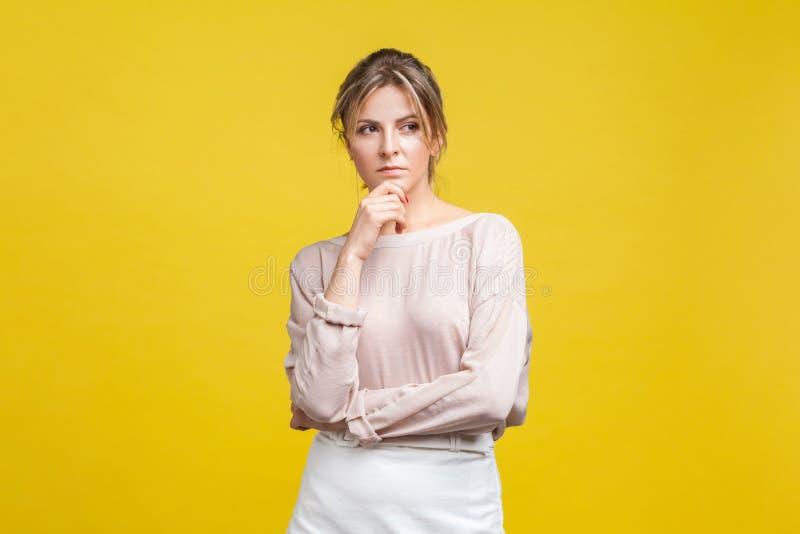 Ritratto di una giovane donna molto pensante con capelli biondi in camicetta di beige, isolata su fondo giallo immagini stock