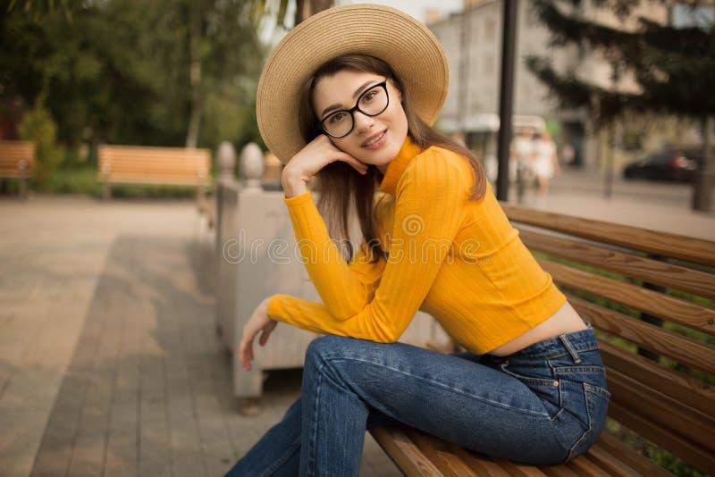 Ritratto di una giovane donna nella citt? Palme nei precedenti Donna intelligente felice con i vetri che si siedono su un banco fotografie stock libere da diritti