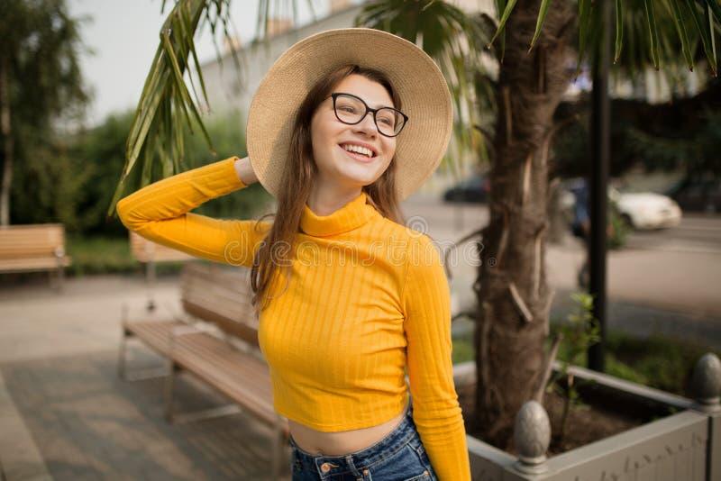 Ritratto di una giovane donna nella citt? Palme nei precedenti Donna intelligente felice con il cappello di vetro i immagine stock
