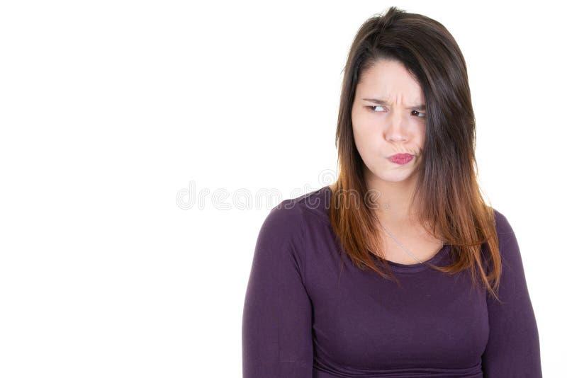 Ritratto di una giovane donna scettica e che pensa da parte lo spazio della copia su fondo bianco fotografia stock