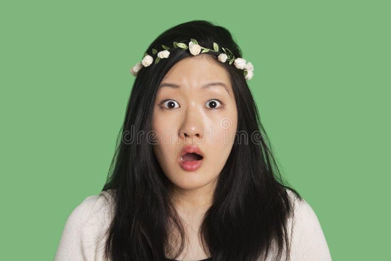 Ritratto di una giovane donna sorpresa sopra fondo verde immagini stock