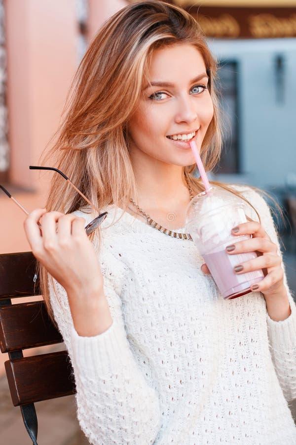 Ritratto di una giovane donna sveglia con i bei occhi azzurri con un sorriso dolce con capelli biondi in un maglione d'annata tri fotografia stock
