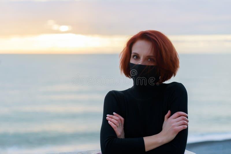 Ritratto di una giovane donna in un maglione nero in freddo contro lo sfondo del mare e cielo al tramonto fotografia stock
