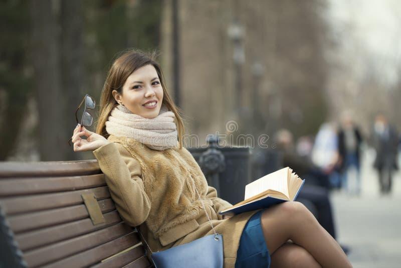 Ritratto di una giovane donna in vetri che legge il libro al parco fotografia stock libera da diritti