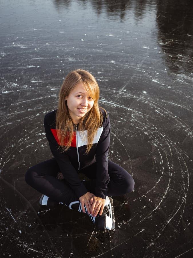 Ritratto di una giovane ragazza pattinatrice sul ghiaccio seduta sul ghiaccio di un lago immagini stock libere da diritti