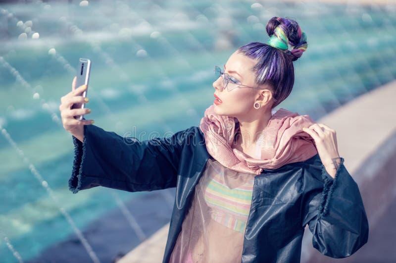 Ritratto di una giovane signora con il sembrare pazzo che prende il selfie degli autoritratti All'aperto urbano con le fontane ne fotografia stock