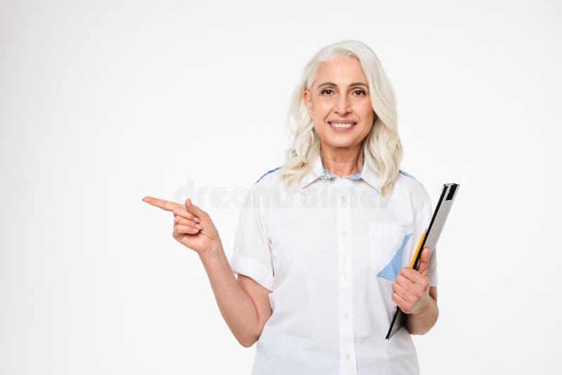 Ritratto di una lavagna per appunti matura felice della tenuta della donna fotografia stock libera da diritti
