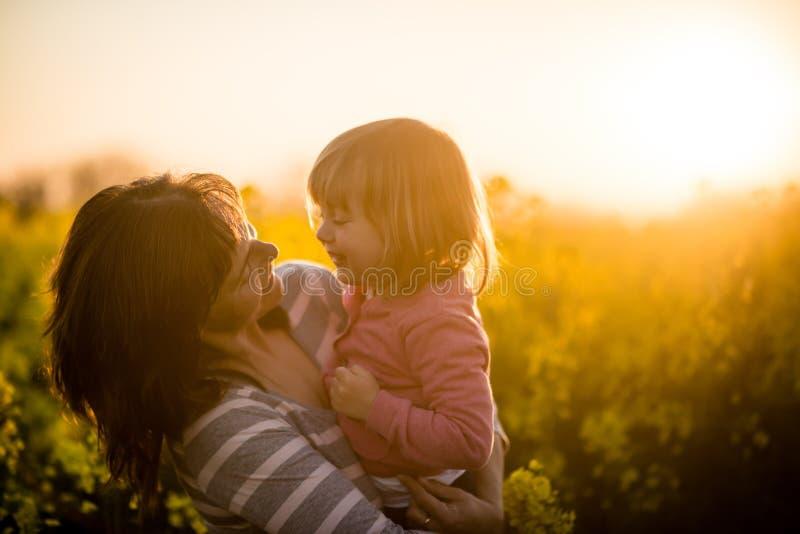 Ritratto di una madre sorridente con la neonata al fondo di tramonto fotografia stock libera da diritti