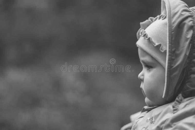 Ritratto di una neonata di undici mesi pensierosa seria su uno sfondo naturale con lo spazio della copia, in bianco e nero immagine stock
