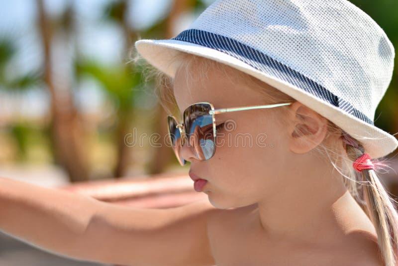 Ritratto di una neonata in vetri ed in un cappello bianco alla località di soggiorno immagine stock libera da diritti