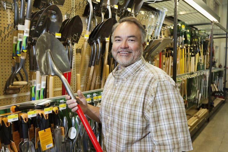 Ritratto di una pala matura felice della tenuta dell'uomo in ferramenta fotografia stock libera da diritti