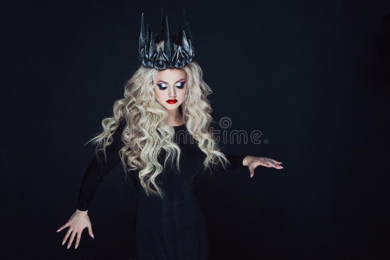 Ritratto di una principessa gotica Bella giovane donna bionda in corona del metallo e mantello nero fotografie stock