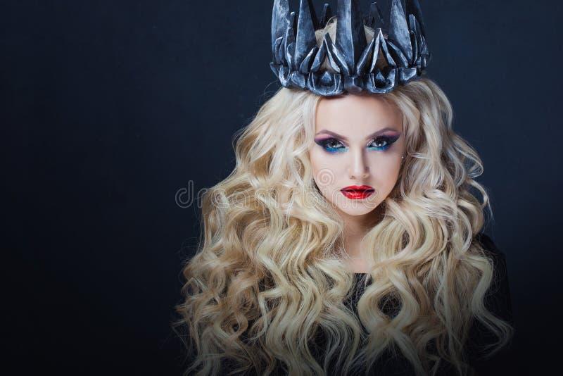 Ritratto di una principessa gotica Bella giovane donna bionda in corona del metallo e mantello nero fotografia stock