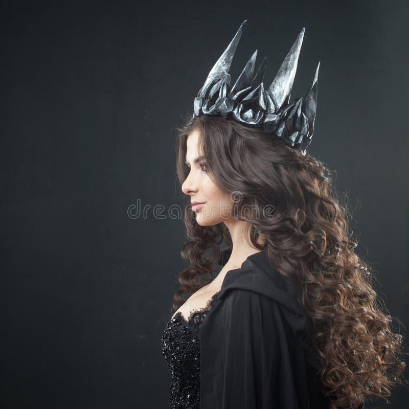 Ritratto di una principessa gotica Bella giovane donna castana in corona del metallo e mantello nero immagini stock libere da diritti