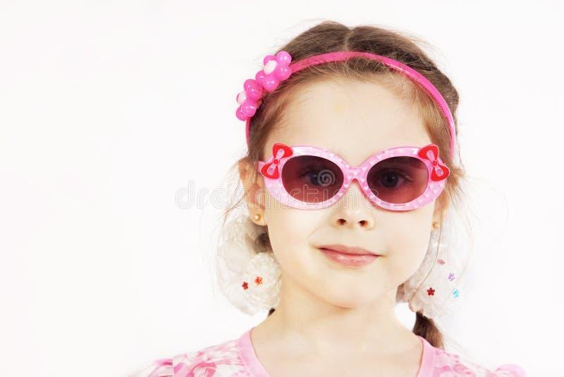 Ritratto di una ragazza abbastanza sveglia che indossa gli occhiali da sole rosa fotografia stock