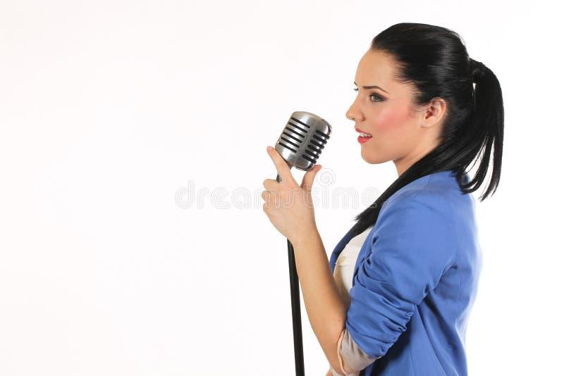 Ritratto di una ragazza affascinante che tiene un microfono e che canta fotografie stock libere da diritti