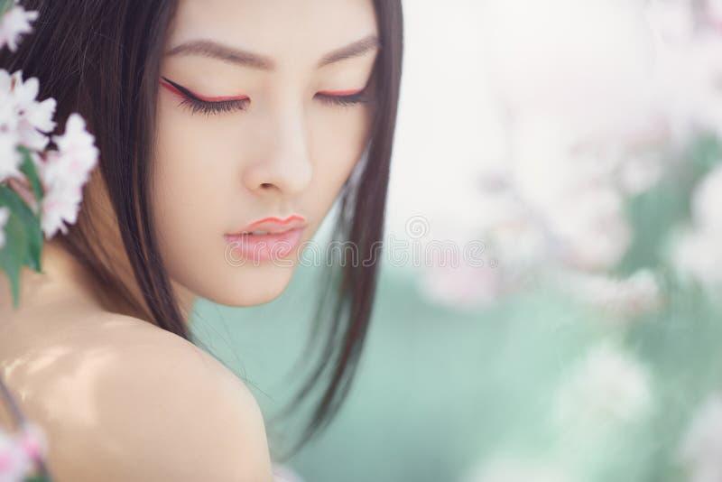 Ritratto di una ragazza asiatica di bella fantasia all'aperto contro il fondo del fiore della molla naturale immagini stock