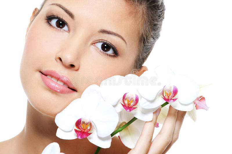 Ritratto di una ragazza asiatica di bellezza con il fiore fotografia stock