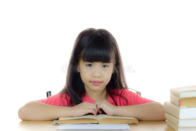 Ritratto di una ragazza asiatica sveglia della scuola sullo scrittorio fotografie stock libere da diritti