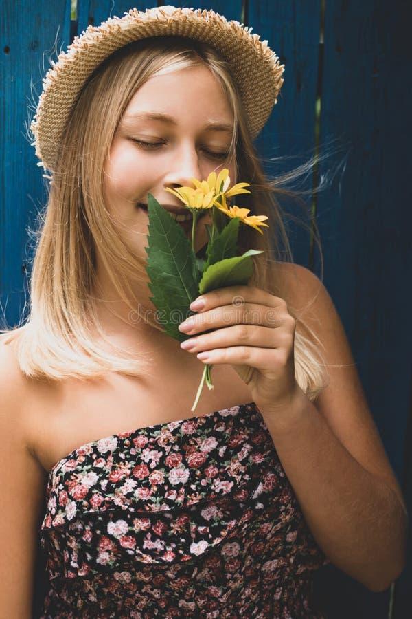 Ritratto di una ragazza bionda carina e bionda con cappello di paglia sorridente e che annusa fiori gialli all'aperto fotografia stock libera da diritti