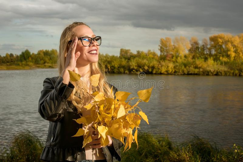 Ritratto di una ragazza bionda con i vetri su un fondo di fogliame giallo in autunno fotografia stock libera da diritti
