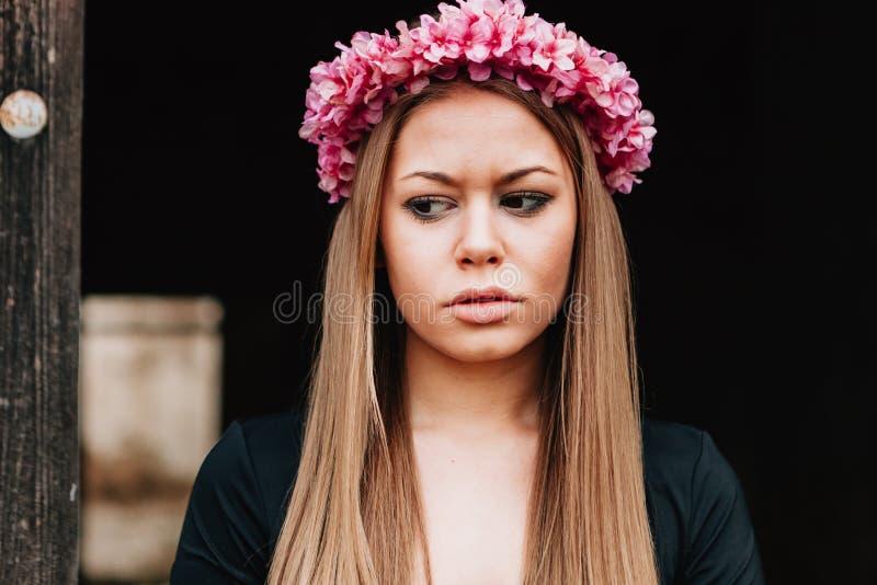 Ritratto di una ragazza bionda con una corona rosa dei fiori sulla sua h immagini stock libere da diritti