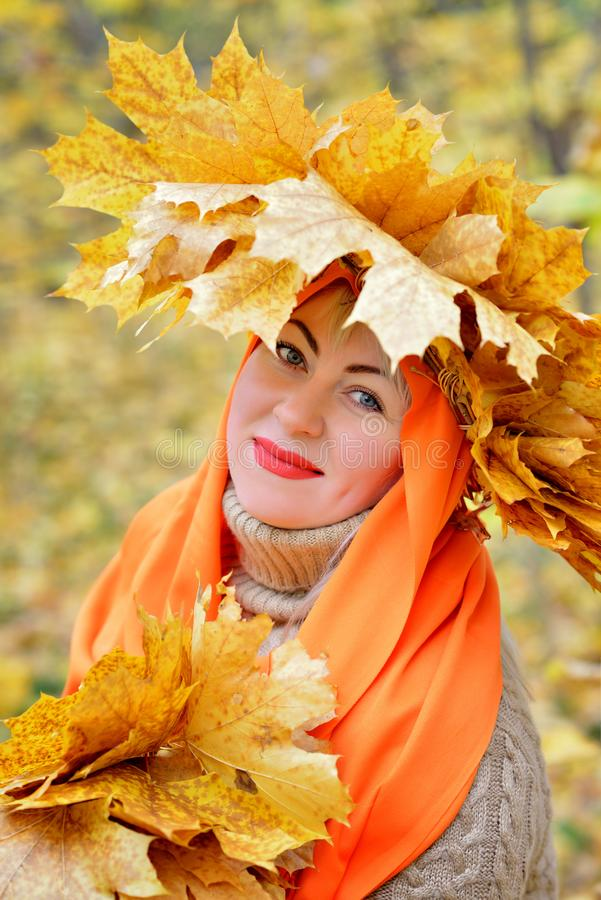 Ritratto di una ragazza bionda più la dimensione in una corona delle foglie di autunno, che si siede in una sciarpa arancio nella fotografia stock libera da diritti