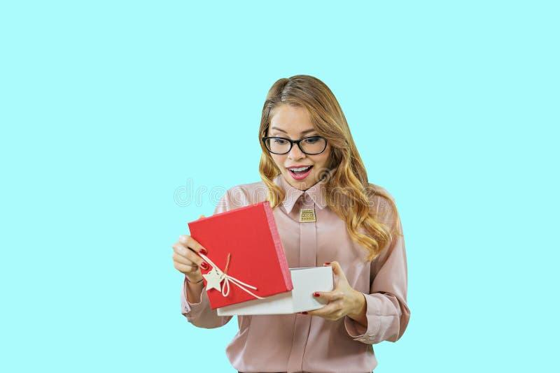 Ritratto di una ragazza bionda sorridente felice che apre un contenitore di regalo con un coperchio rosso su un fondo isolato blu immagini stock