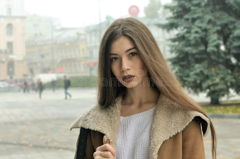 Ritratto di una ragazza che cammina intorno al quadrato in una città nebbiosa immagine stock