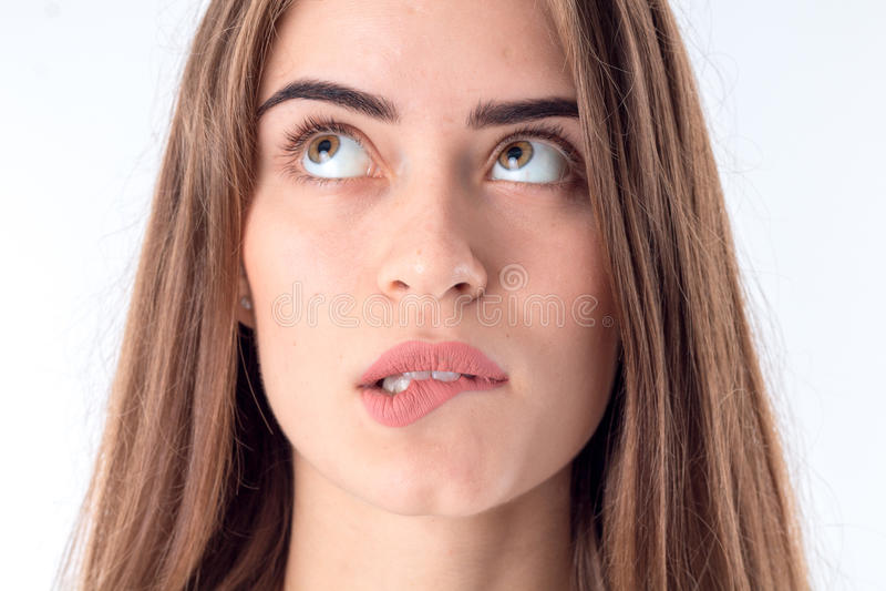 Ritratto di una ragazza che morde il labbro ed alzata lei occhi su vicino fotografia stock