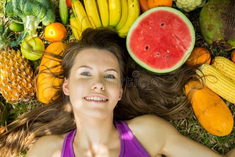 Ritratto di una ragazza che si trova sull'erba con la frutta e le verdure immagini stock