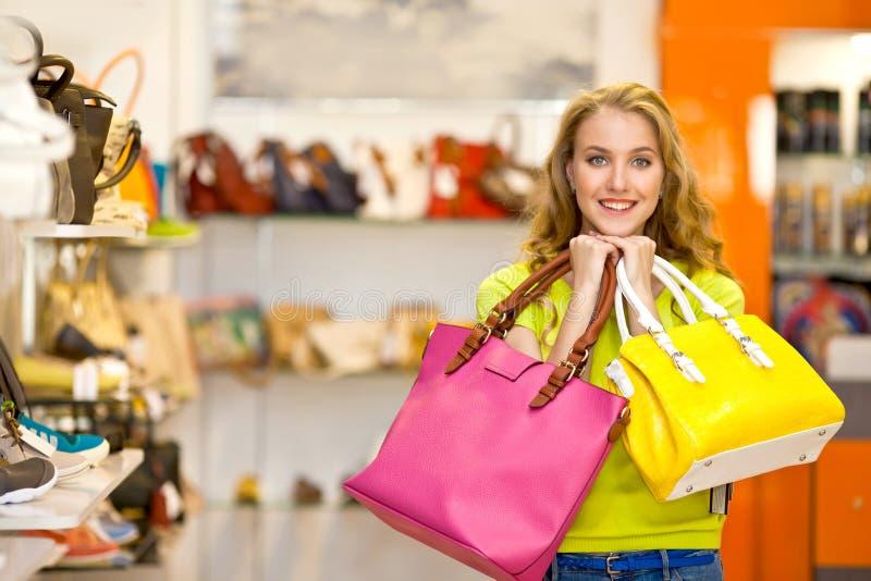 Ritratto di una ragazza con le borse di cuoio in sue mani nel centro commerciale fotografie stock libere da diritti