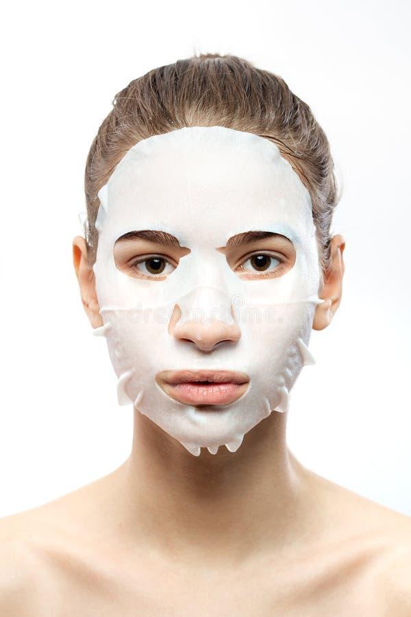 Ritratto di una ragazza con una maschera di protezione d'idratazione bianca sui precedenti bianchi immagine stock